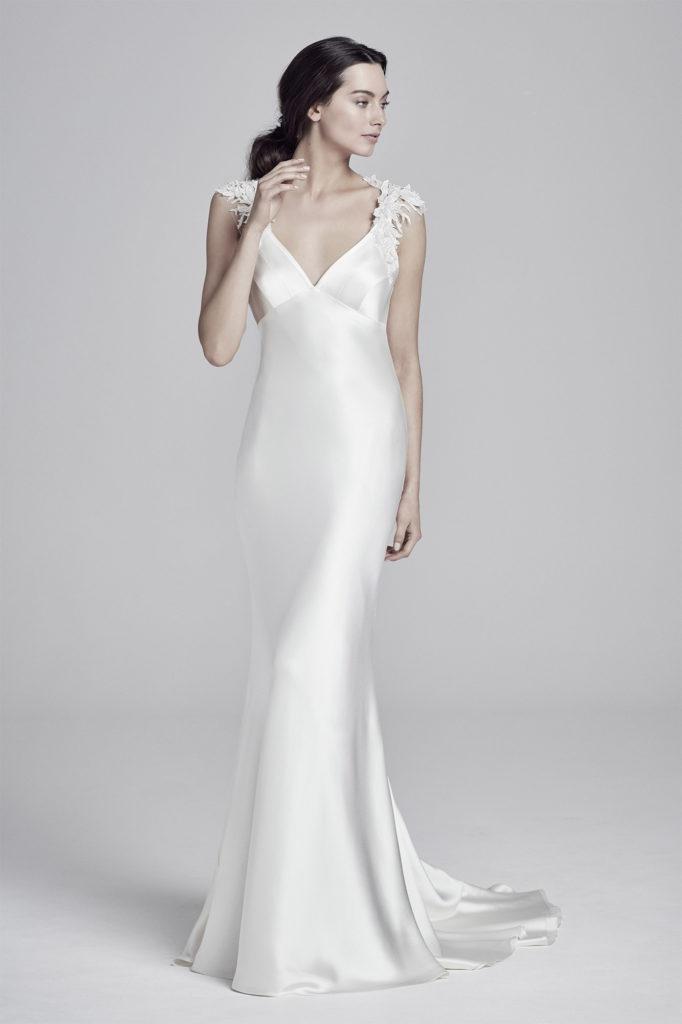 Petite Irish bride in floor length, white satin Suzanne Neville wedding dress with lade detail shoulder straps and empire waistline