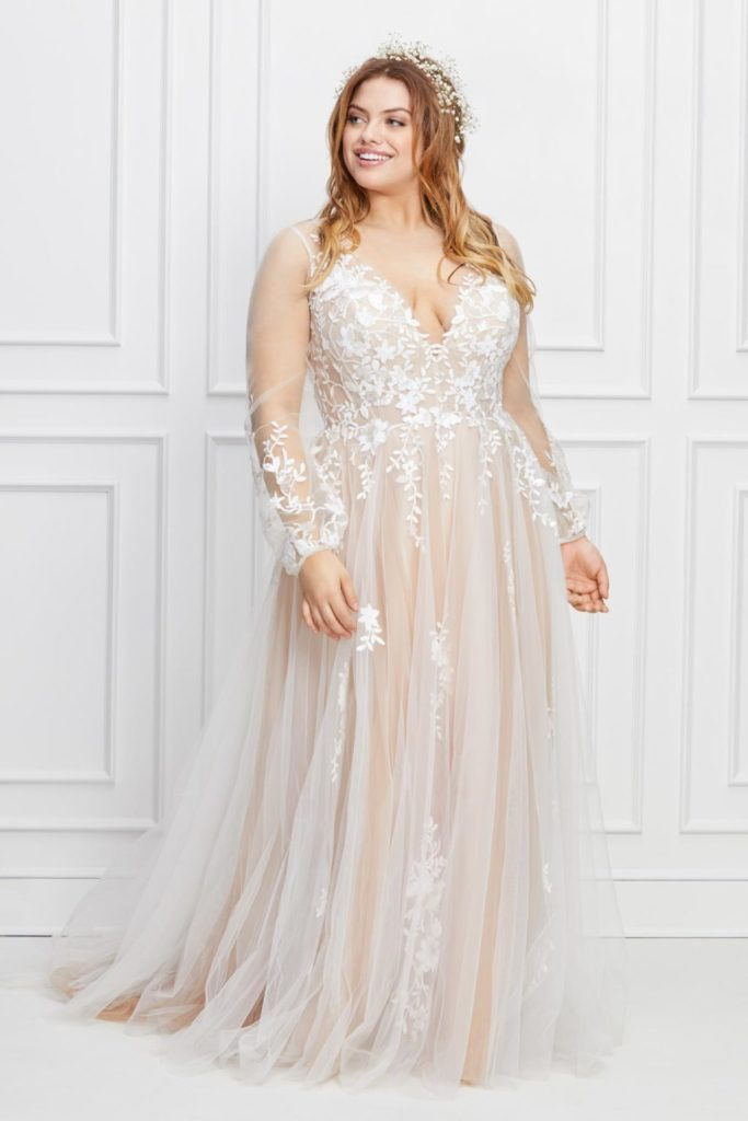 Plus size bride in white and nude, floor length Willowby wedding dress with floral applique, sheer sleeves and deep v neck