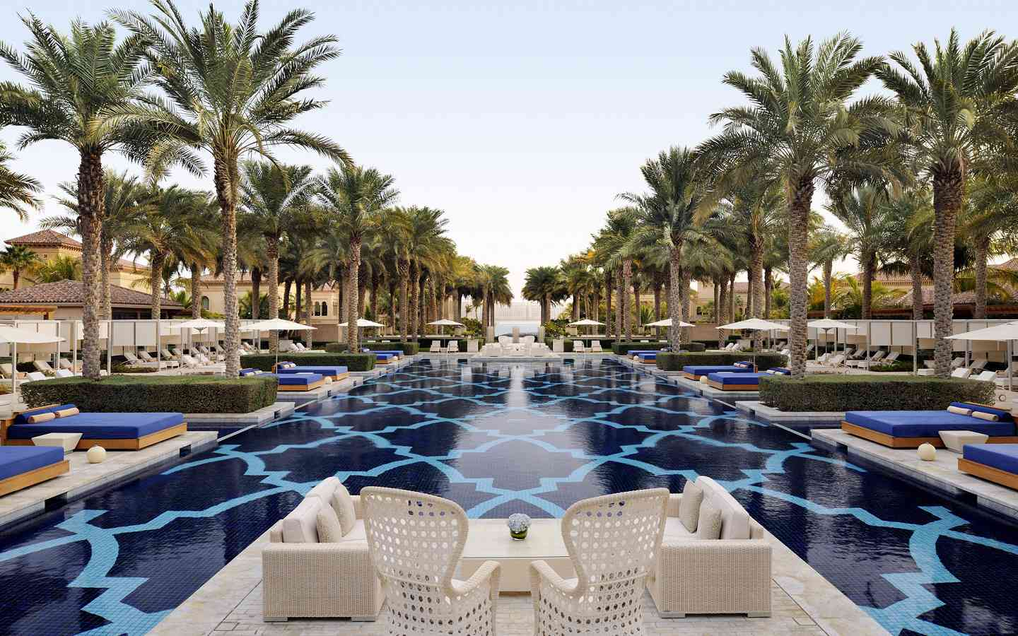 Picturesque blue tiled resort pool in Dubai, bordered with sunning beds and palm trees