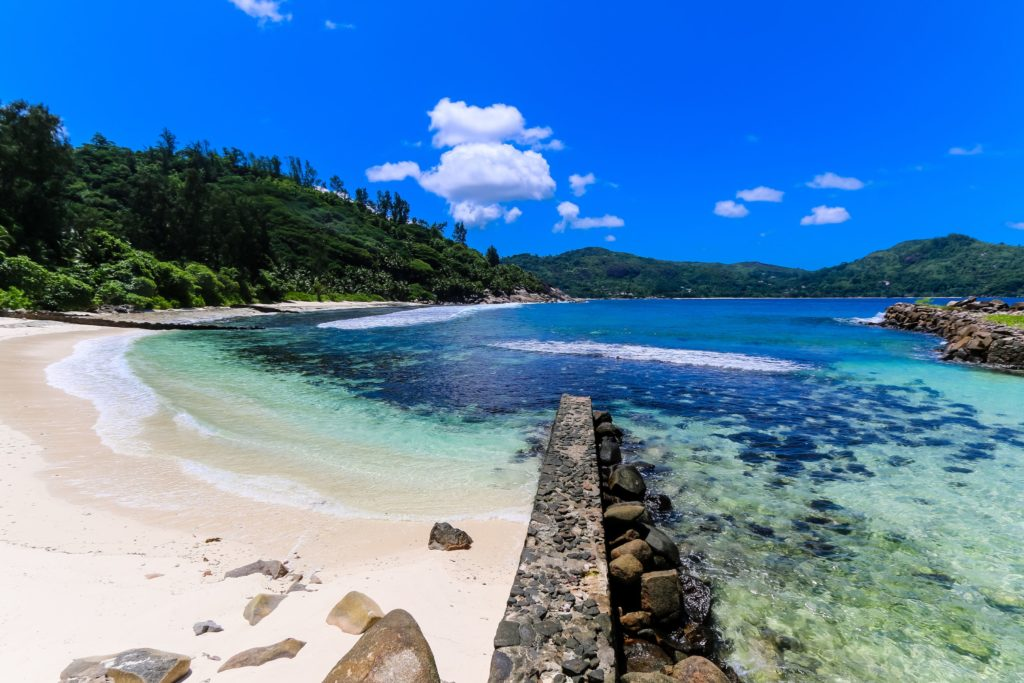 A secluded beach in Seychelles with very blue ocean water, an equally blue sky and a stone wall leading into the ocean
