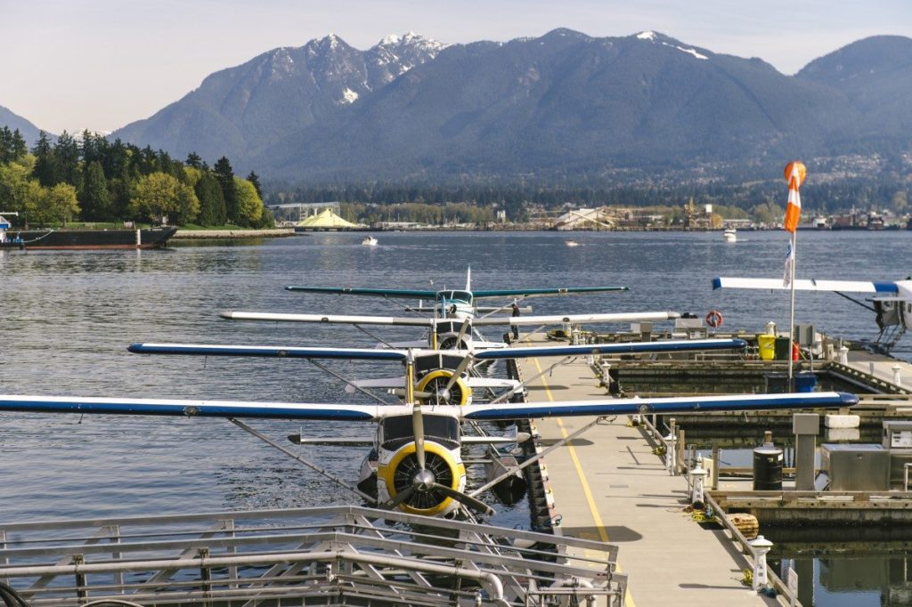 Four seaplanes docked at a Vancouver harbor, a snow capped mountain range accents the background