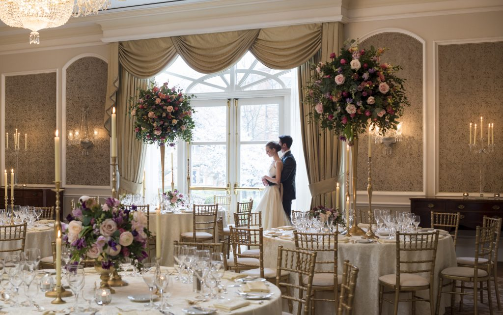 Bride and Groom standing in banqueting hall at The InterContinental Dublin. The room is set up for the wedding celebration with beautiful floral centerpieces on each table.