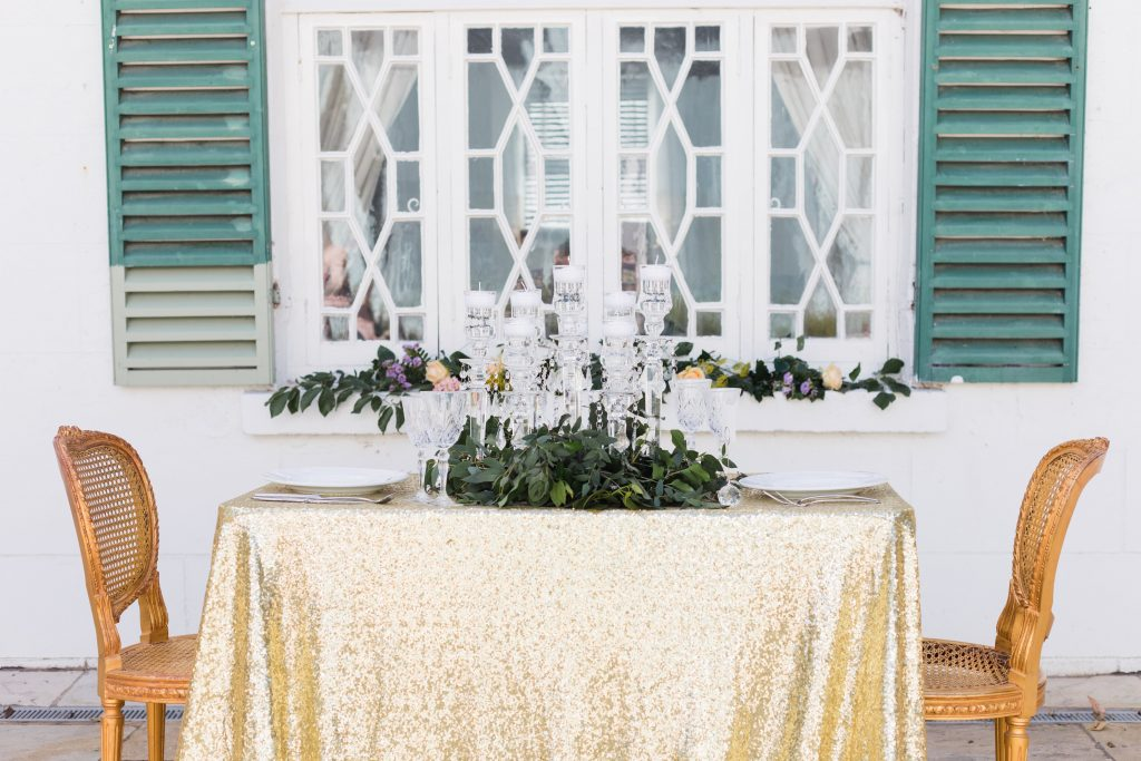 table setting outside with crystal glasses and leaves as the centerpiece