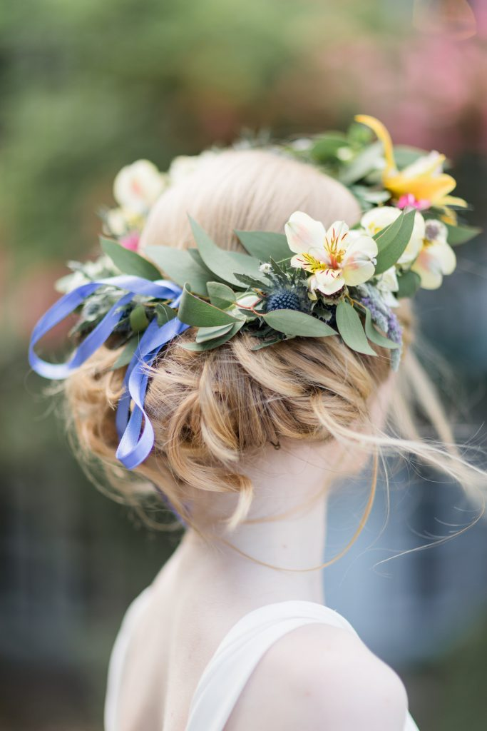 back view of a flower crown with a purple bow and yellow flowers