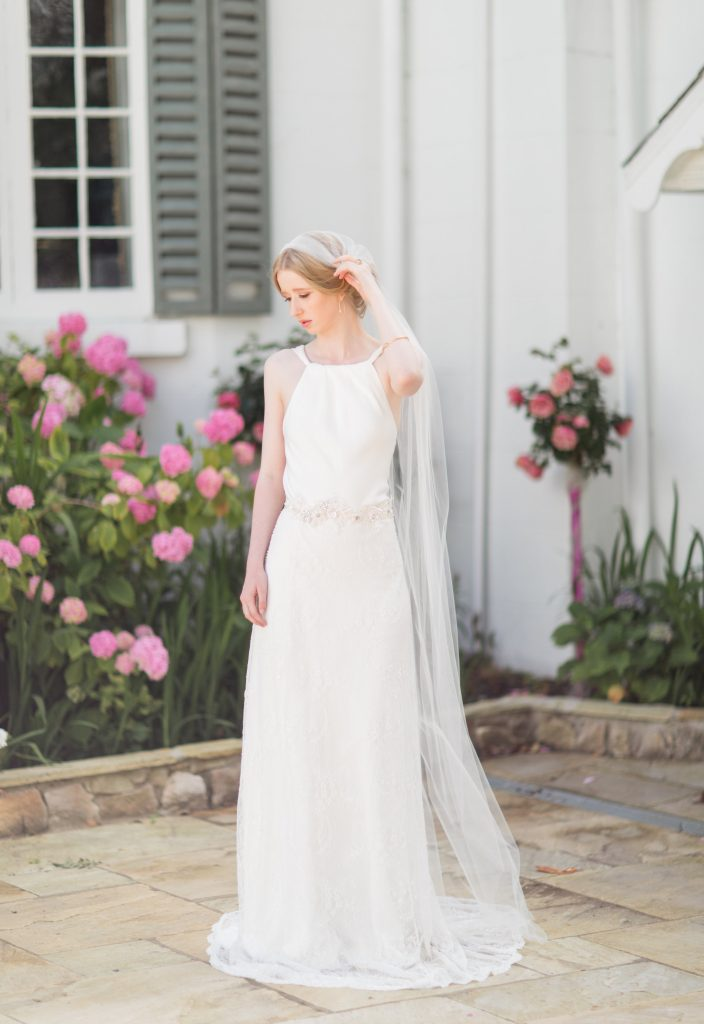 the bride wears a simply elegant white dress with a crystal detailed belt