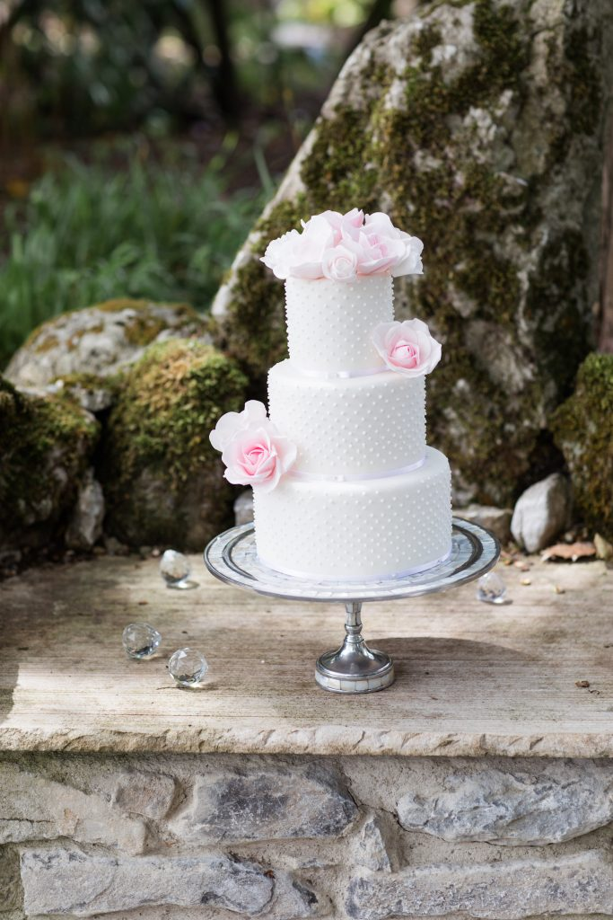 white wedding cake with dot decorations and pale pink roses