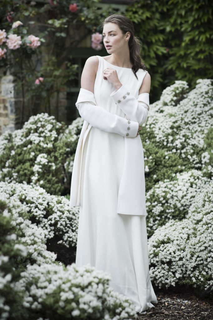 Cliff at Lyons shoot. Spring/summer 19 Bridal Inspiration. Bride amounst white flowers wearing a simple white dress and coat.
