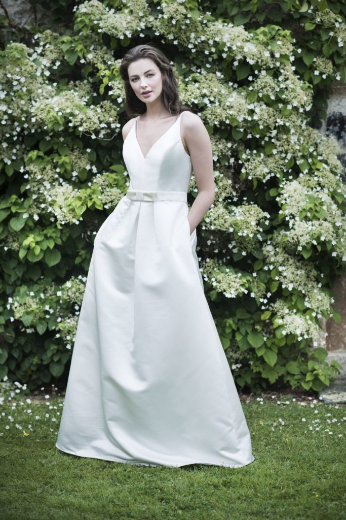 Bride in simple a-line dress against greenery.