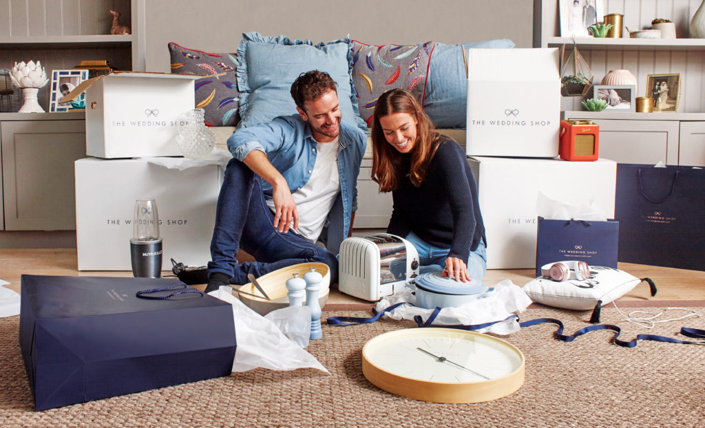 A couple appear to be sitting on the floor opening gifts from the wedding shop, these include a toaster, a clock, a bowl, salt and pepper shakers and a blender