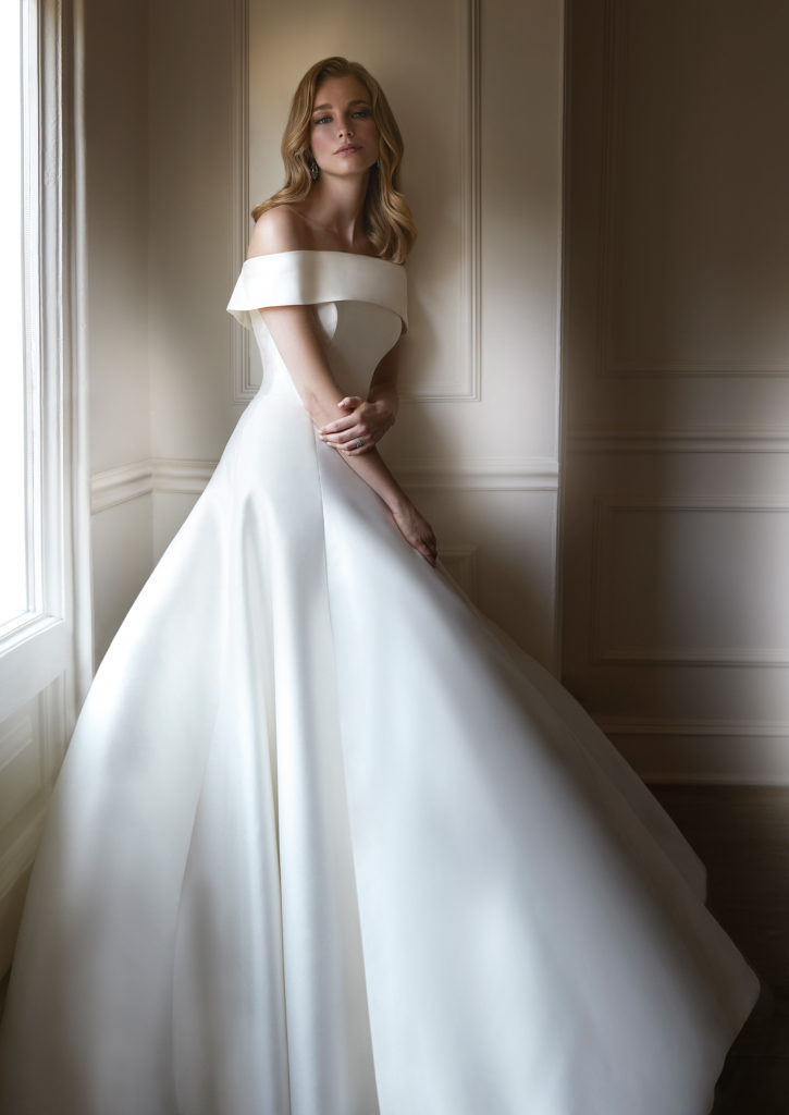 White floor length, off the shoulder satin dress by Caroline Castigliano