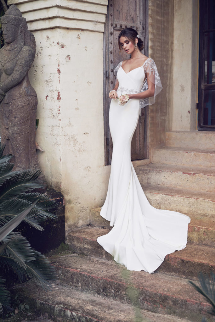 Fitted, floor length, white silk dress with lace cape sleeves by Anna Campbell