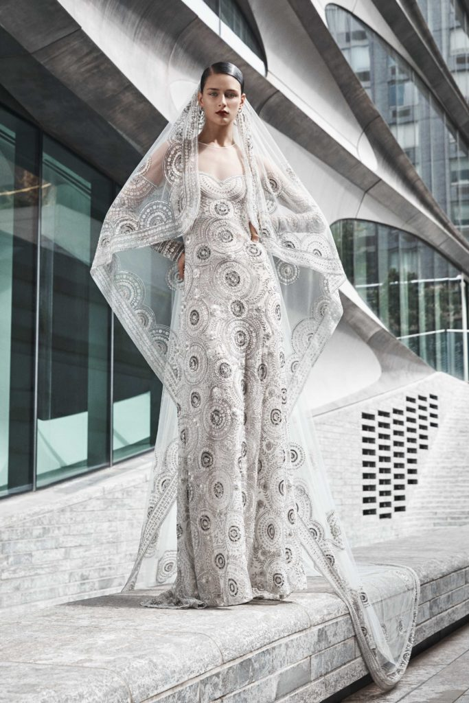 Lean bride in highly embellished silver and white column Naeem Khan wedding dress with matching veil