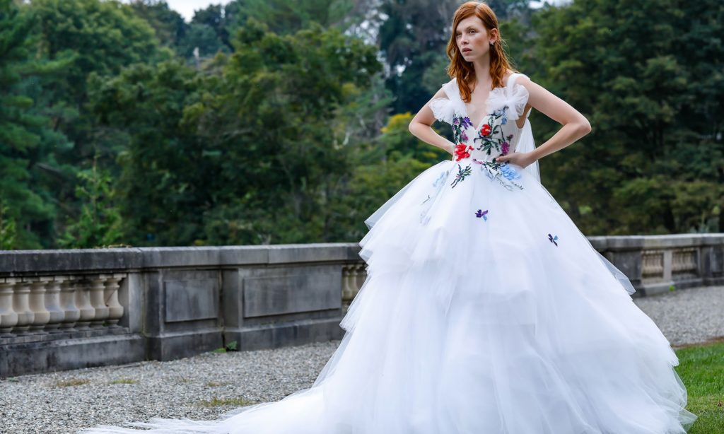 White, floor length, tiered dress with red, blue, purple and green floral embroidery on the bodice by Monique Lhuillier