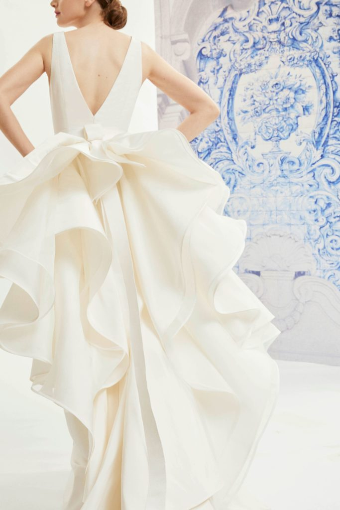 White, floor-length dress with large bustles back detail and deep back v by Carolina Herrera