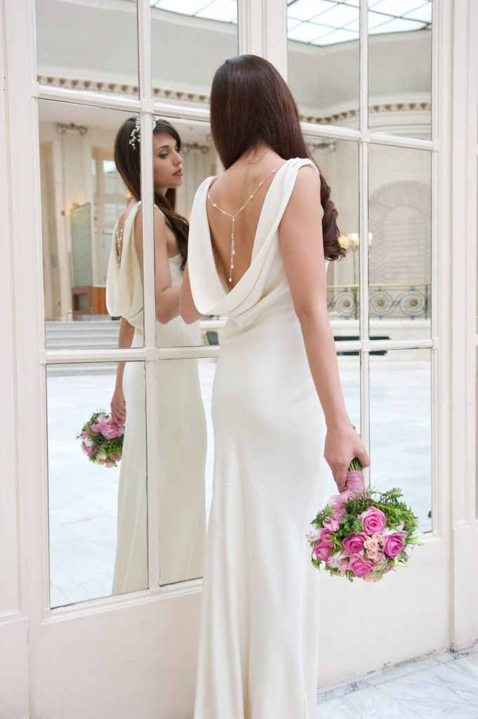 White, figure hugging, floor-length dress with cowl neck accentuating the back by Sabrina Motesem