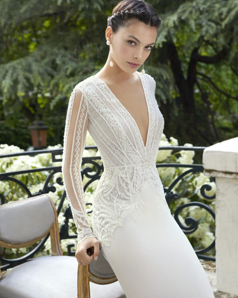 White, fitted, floor-length dress with lace embellishments, plunge neckline and long sleeves by Rosa Clara