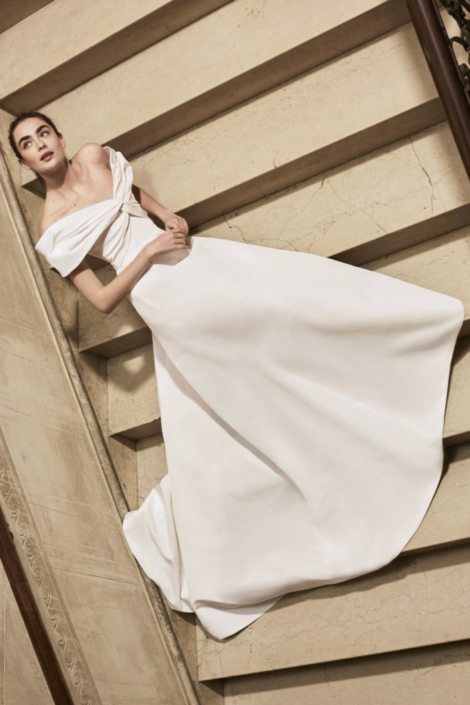 White, floor-length, satin, off the shoulder dress with knotted bodice details by Carolina Herrera