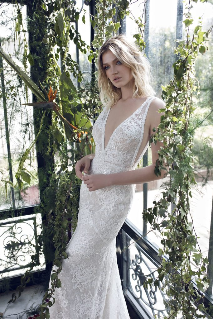 White, fitted, lace floor-length dress with deep plunging neckline and plunging armpit slits by Limor Rosen