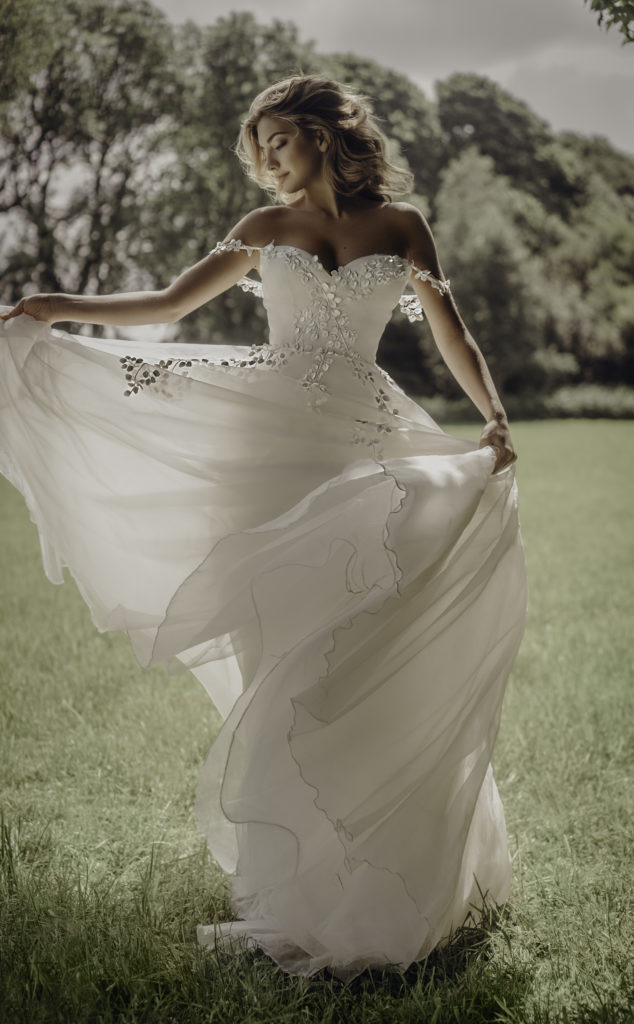 White, floor-length dress with petal embellishments, off the shoulder straps and a sweetheart neckline by Stephanie Allin