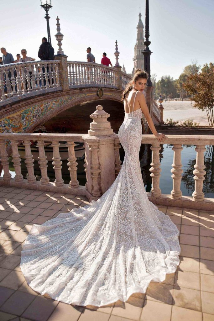 White, lace, floor-length, fitted dress with large circular train and spaghetti straps by Berta