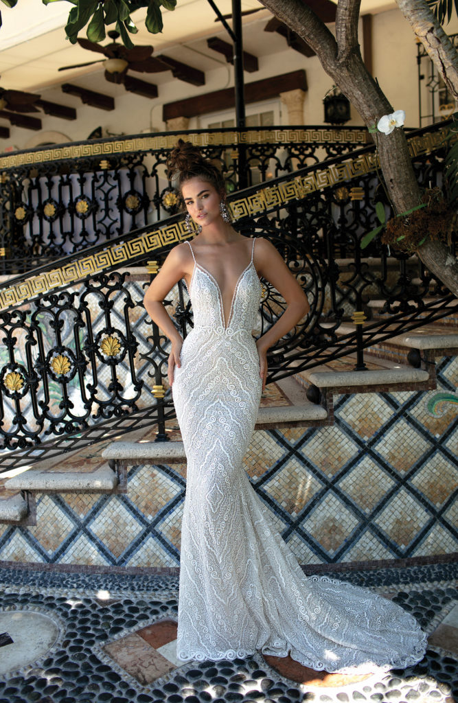 White, floor-length dress with deep plunging neckline, silver beaded details and bustle hook by Berta