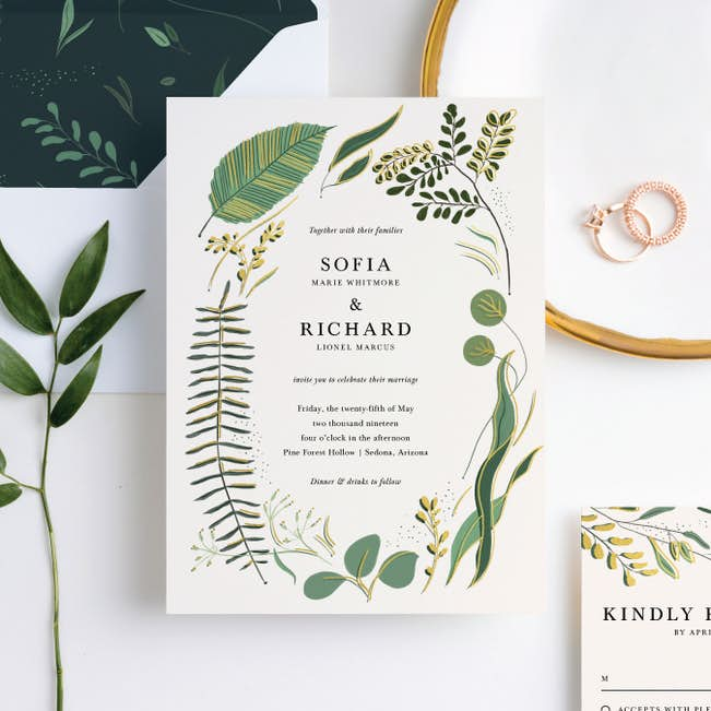 A paper invitation printed on white card with hand drawn greenery framing the text which displays the couples names and details of their wedding