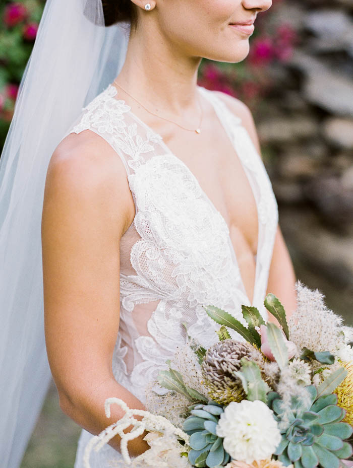 Bride is white lace V neck gown and white veil standing portrait to the camera holding a large bouquet of flowers and succulents.