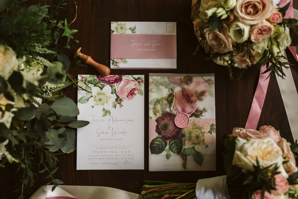 Real Wedding at Ballybeg House. Flatlay of the couples wedding stationery. The colour scheme is dusty pink and purple with a floral pattern. Vintage feel.