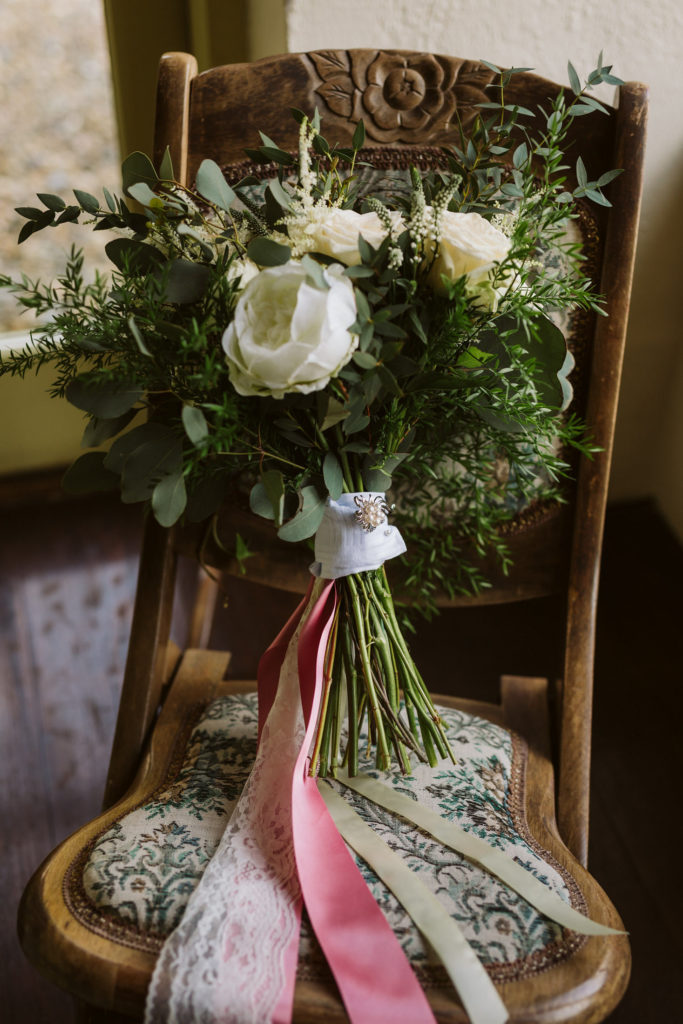 Real Wedding at Ballybeg House. Floral wedding bouquet sitting on chair. The bouquet is tied with a ribbon sash made up of pink and white satin ribbon.