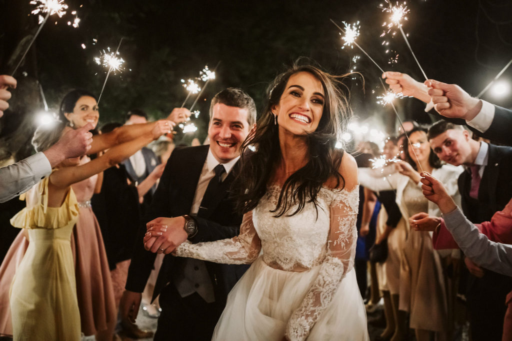 Real Wedding at Ballybeg House. Bride and groom are centre picture with their guests on either side of them. Each guest is holding a lit sparkler. It is nighttime. The couple appear to be running and look happy, both are smiling and carefree.
