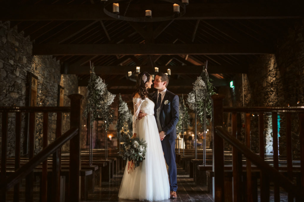 Real Wedding at Ballybeg House. Bride and Groom stand kissing in the ceremony room. The pews and floral decorations frame the couple on either side.