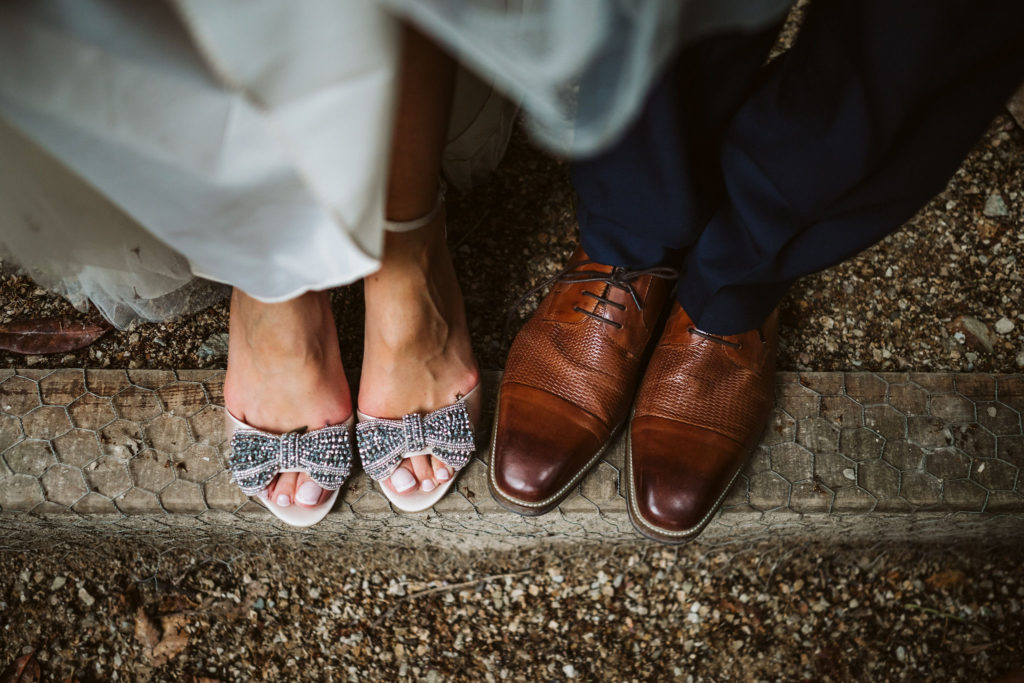 Real Wedding at Ballybeg House. Picture of the bride and grooms feet. The groom is wearing brown leather tie up shoes while the bride is in an open toe sandal. Her bridal shoes are embellished with a beaded bow pinned to the front.