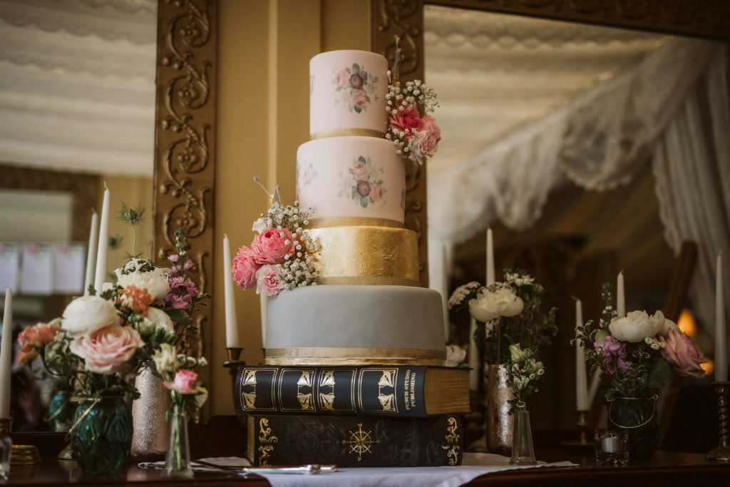 Real Wedding at Ballybeg House. Four tier wedding cake with grey, gold and a floral pattern. The cake is decorated with real flowers: roses and babies breathe.