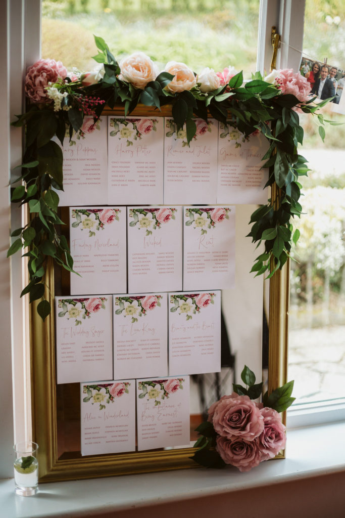 Real Wedding at Ballybeg House. Board sat in the window with table number attached. There are flowers and greenery surrounding the top of the board.