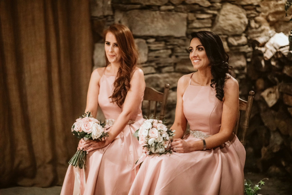 Real Wedding at Ballybeg House. Bridesmaids sitting during ceremony. They are wearing dusty pink tea length bridesmaids dresses and are carrying small pink rose bouquets.