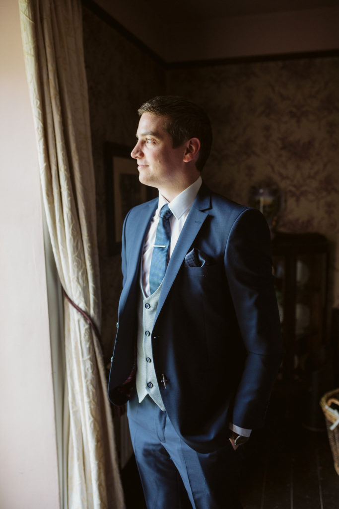 Real Wedding at Ballybeg House. Groom stands pensively at a window look out.