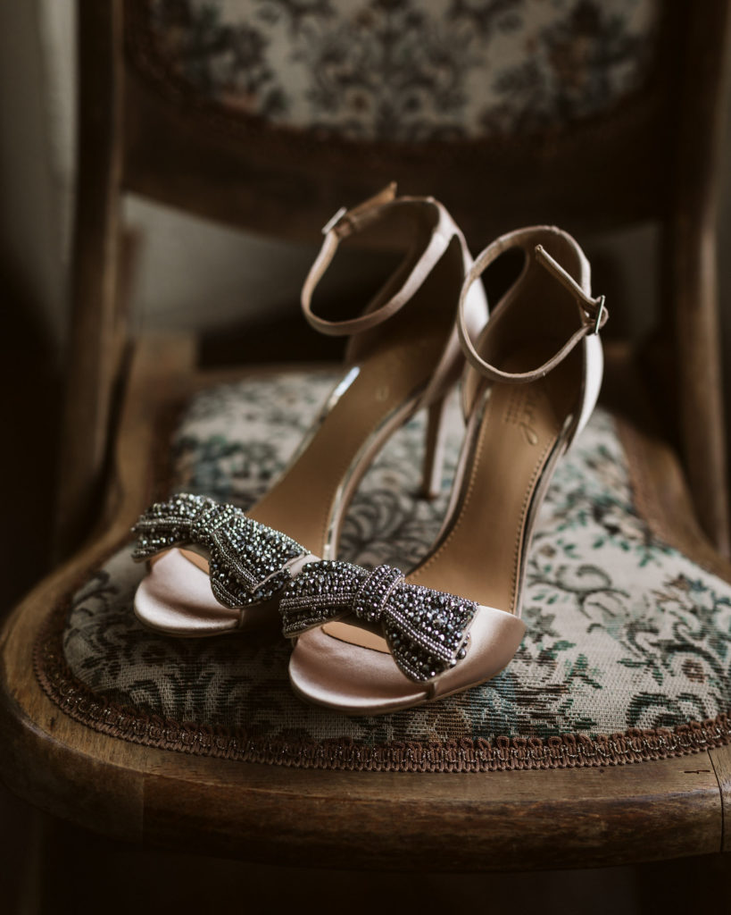 Real Wedding at Ballybeg House. Close up of the brides wedding shoes. They are nude/gold in colour and they are adorned with an embellished bow on the front.