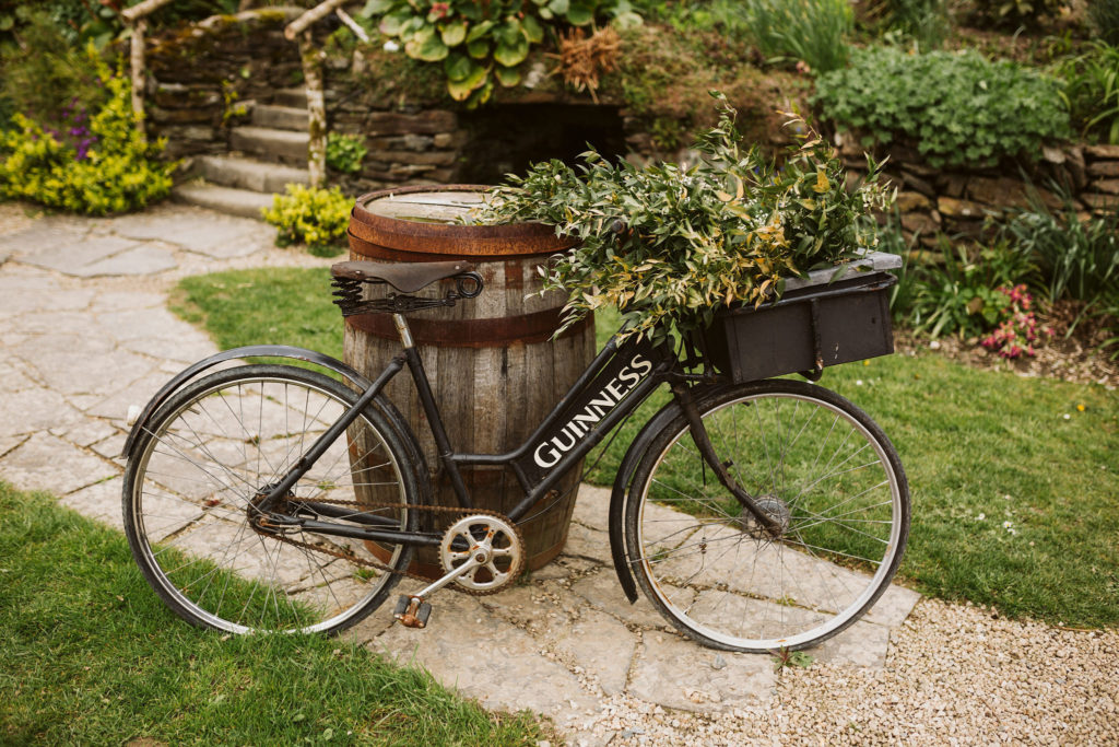 Real Wedding at Ballybeg House. Black vintage bicycle outside the venue sat propped against a barrel. There is a basket in the front and it is filled with greenery.