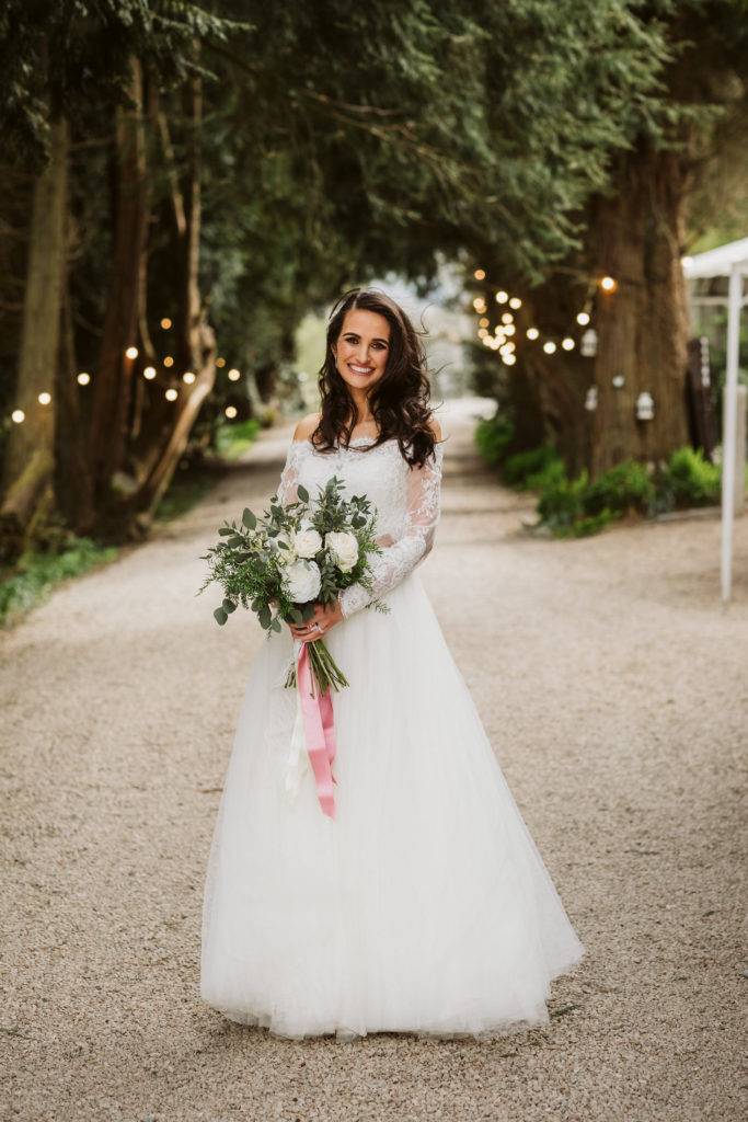 Real Wedding at Ballybeg House. Bride stands alone on gravel path outside the venue. There are trees on either side of her and there are fairylights visible in the background. She is smiling and holding her large floral wedding bouquet.
