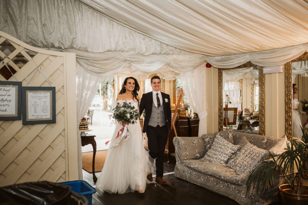 Real Wedding at Ballybeg House. Bride and Groom enter the dining hall at their reception. They are hand and in and the bride is holding her larger floral wedding bouquet. The room is decorated with washes of material in white.