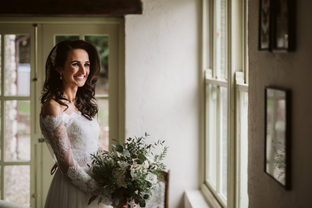 Real Wedding at Ballybeg House. The bride is standing at a window, she is dressed for her wedding in her wedding gown and is holding her flowers. She is smiling and looks happy.