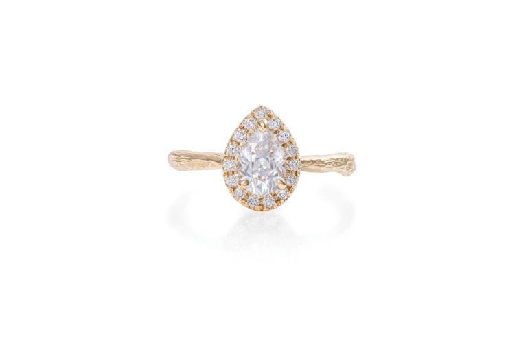 Chupi Moissanite ring, gold in a tear drop shape with pave diamonds surrounding.