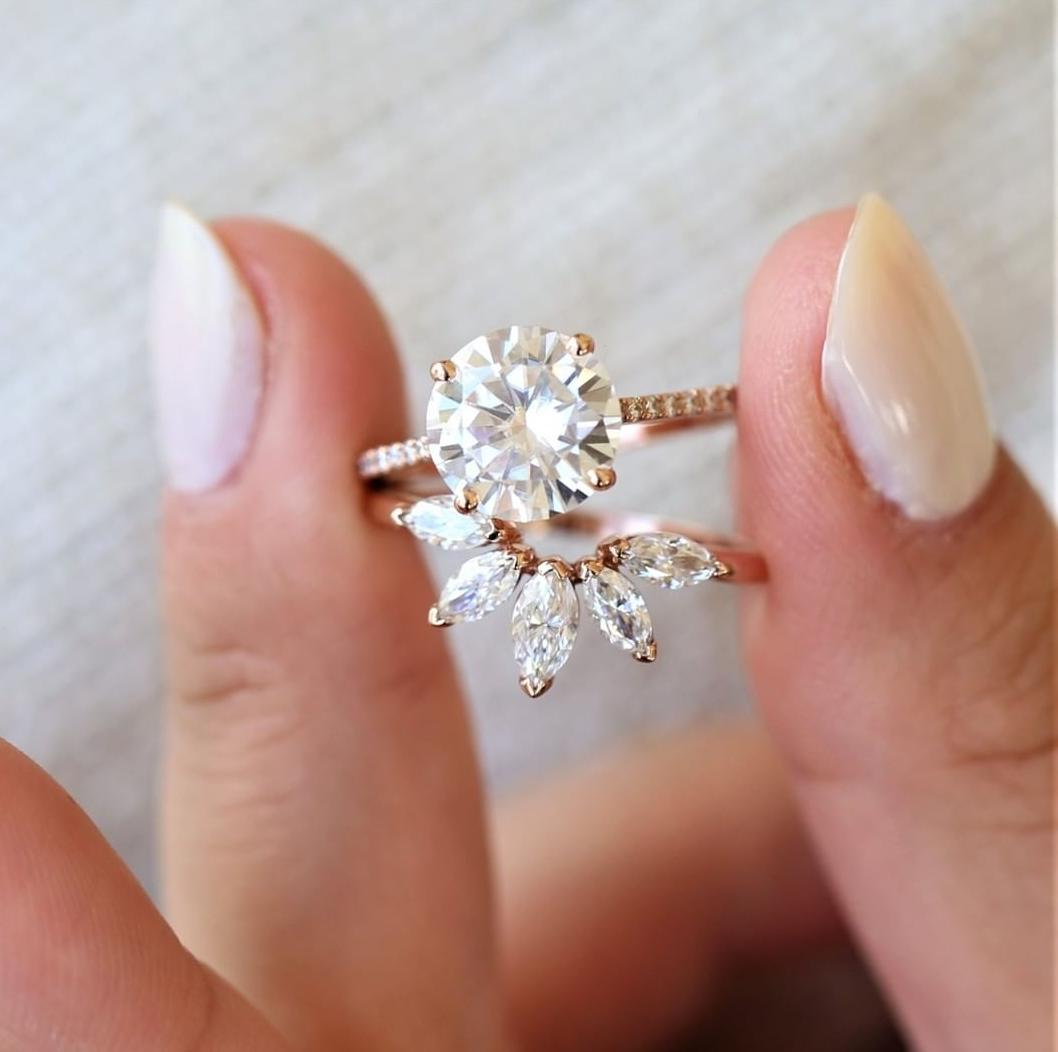 A bridal set featuring a moisaannite solitare on a pave band and a star burst wedding band.