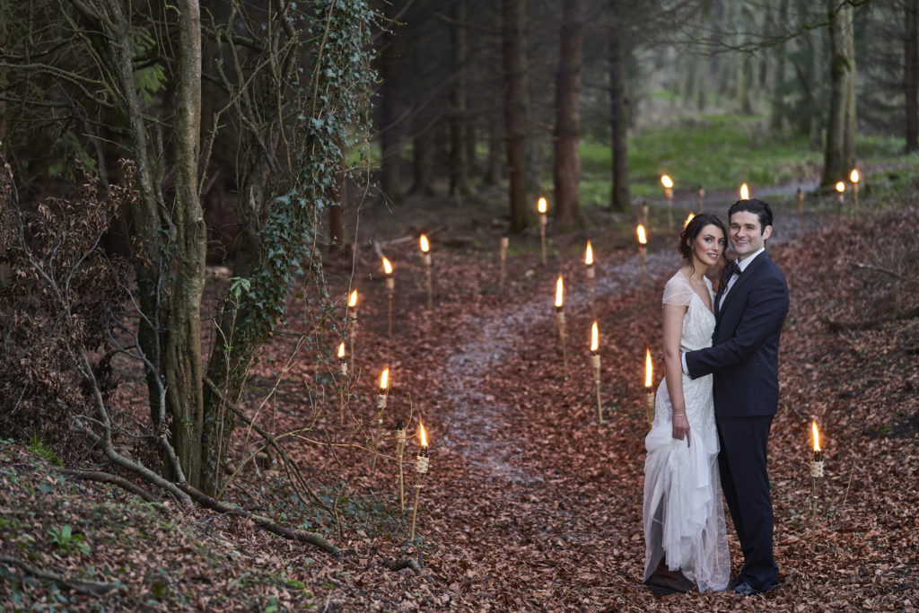 Bride and groom standing on leaf filled pathway. The leaves are brown and either side of the path is tree lines. There are lights lighting up the pathway. Location The Johnstown Estate.