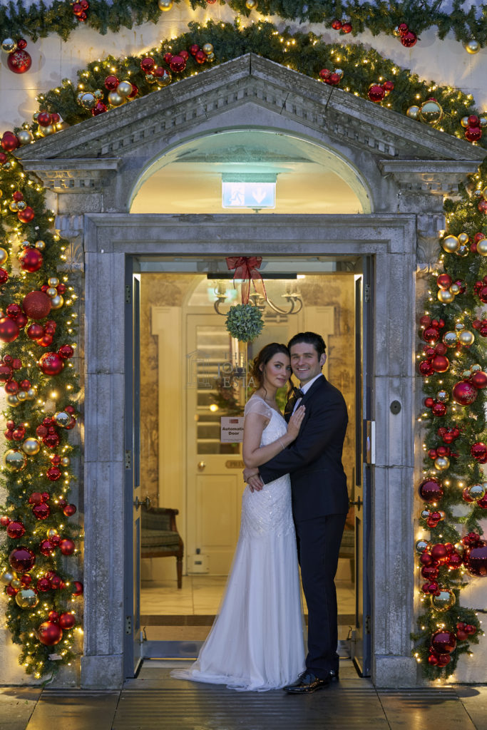 Bride and Groom standing at main door of Johnstown Estate. The door is surrounded by Christmas decorations and lights.