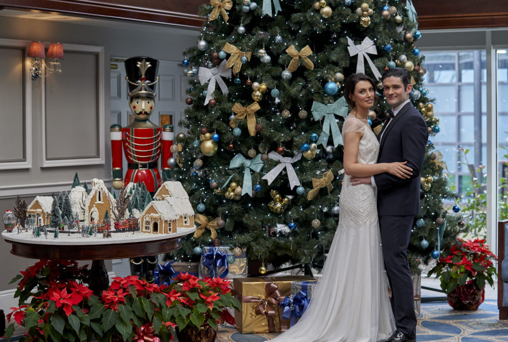 Bride and Groom standing at the Christmas tree at Johnstown Estate