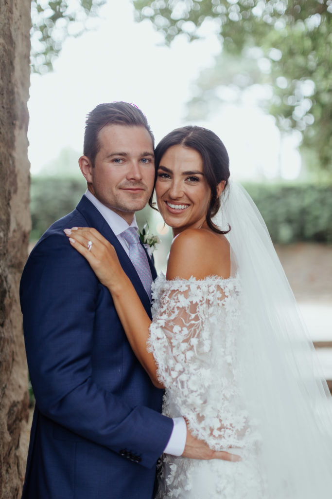 Irish bride and groom embrace while looking into the camera. The groom is wearing a royal blue suit while the bride is in an off the shoulder white wedding dress with a long white veil