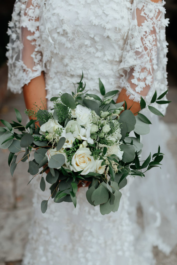 A shoulder down shot of the Irish bride in a white floral applique dress holding a large bouquet of white roses and greenery
