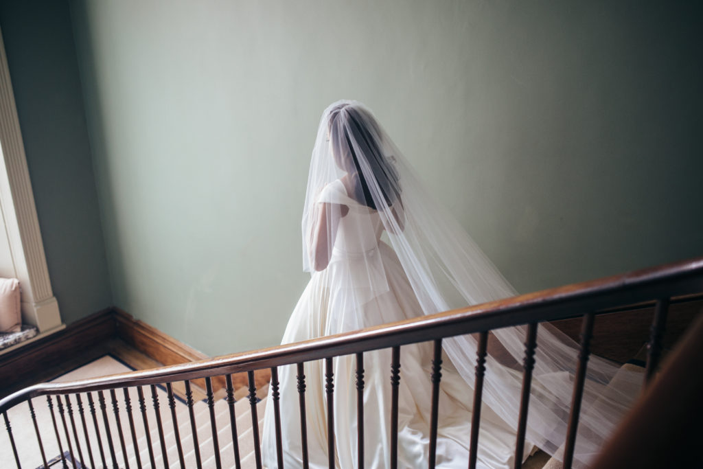 Bride is walking down a flight of stairs in a large white wedding dress and long white veil. The veil is draped over her face and also drapes down her back and onto the stairs