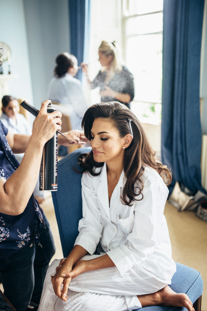 Dark haired bride sits on a cushioned blue chair in white pajamas with her eyes closed as hairspray is sprayed onto her styles hair. In the background a bridesmaid in a white robe is getting her makeup done